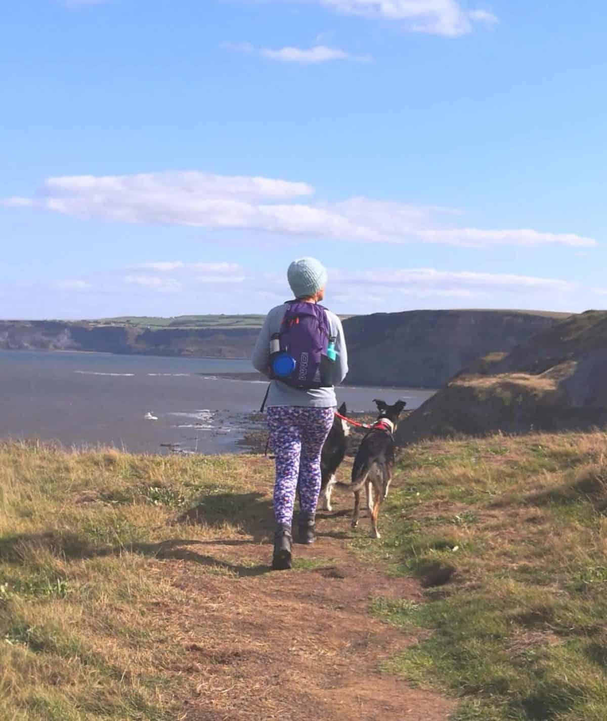 A photo of Anna from Feed Your Passion walking with her dogs