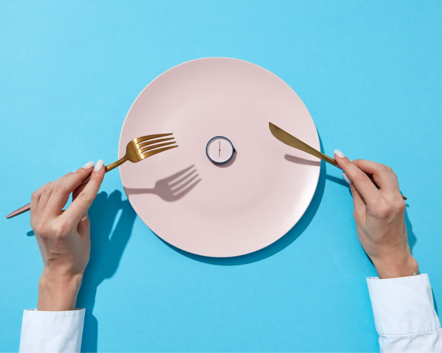 Photo of an empty plate, with a small clock sitting on the centre of the plate. To represent fasting.